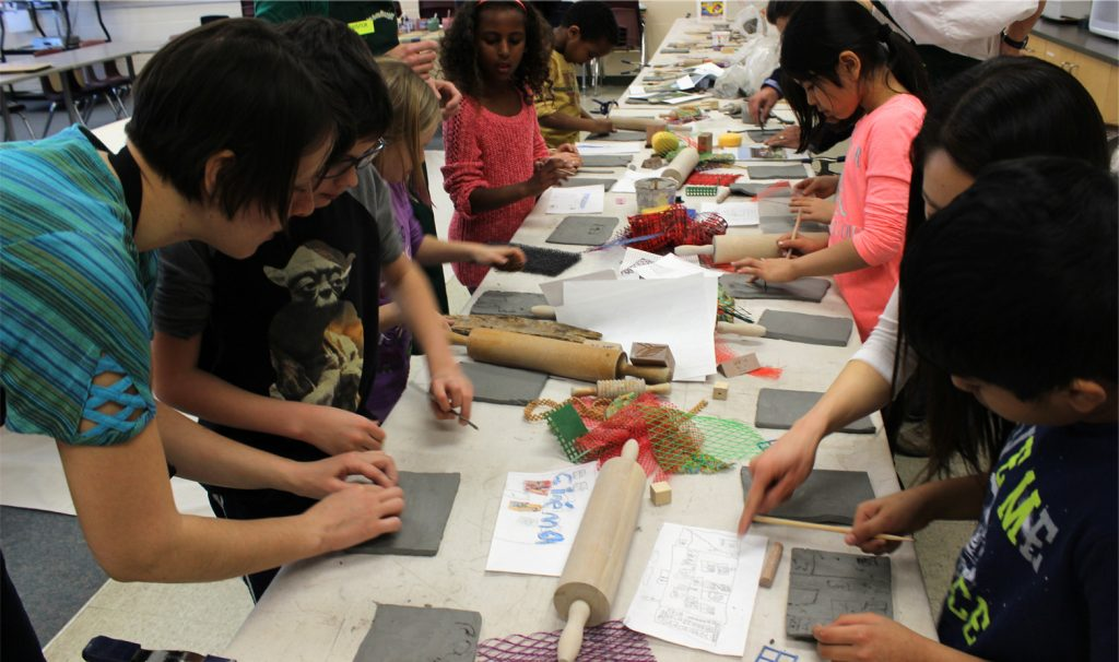 Artist Alexandra Iorgu working with a group of students using clay.